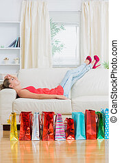 Woman relaxing on the sofa after shopping