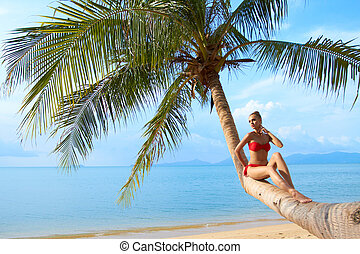 Woman relaxing on the trunk of a palm tree