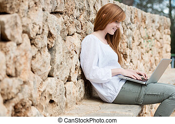 Woman relaxing typing on her laptop