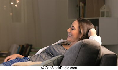 Woman relaxing watching tv in the night - Happy woman...