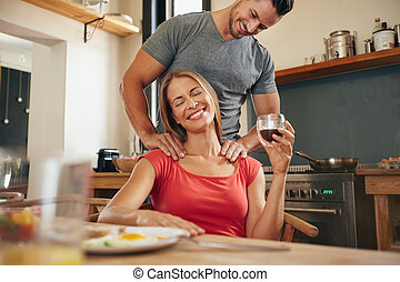 Woman relaxing while man massaging her shoulders