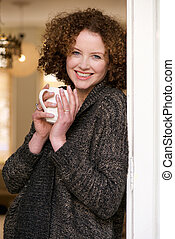 Woman relaxing with a cup of tea at home