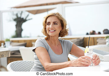 Woman relaxing with a drink of water at outdoors restaurant