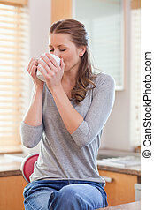 Woman relaxing with coffee in the kitchen