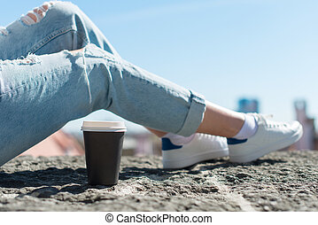 Woman relaxing with cup of coffee in the old town.