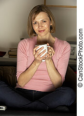 Woman Relaxing With Cup Of Coffee Watching Television