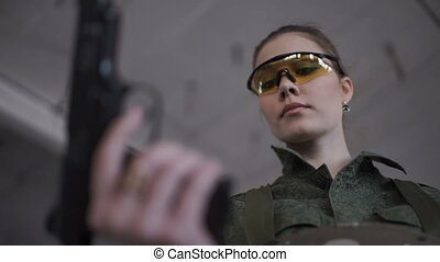 Woman reloads weapons - A woman in goggles reloads weapons...