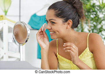 woman removes cosmetics with cotton swab