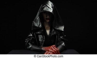 Woman removing black hood - Footage of woman in black...