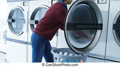 Woman removing clothes from washing machine 4k - Woman...