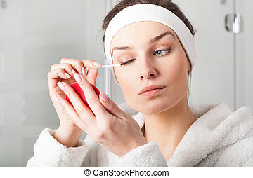 Woman removing eyes make-up - Young woman in robe removing ...