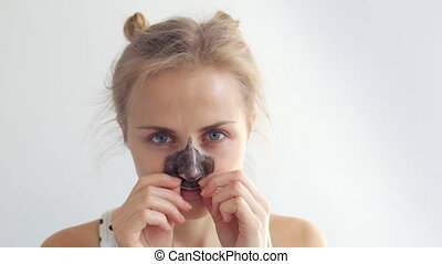 Woman removing her black mask from her nose. Blackhead and...