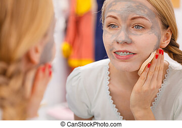 Woman removing mud facial mask with sponge