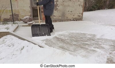 Woman removing snow in yard