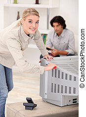 Woman removing the back of a tv set