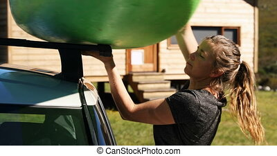 Woman removing the kayak from car roof rack 4k - Close-up of...