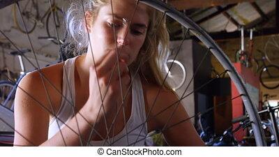 Woman repairing bicycle at work shop 4k - Beautiful woman...