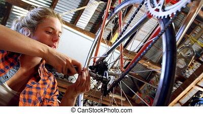 Woman repairing bicycle at workshop 4k - Beautiful woman...
