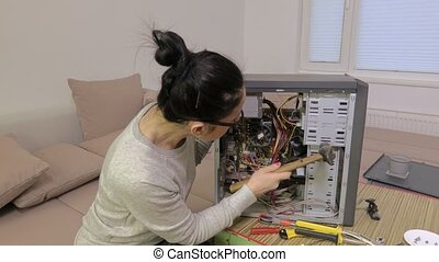 Woman repairing computer with hammer