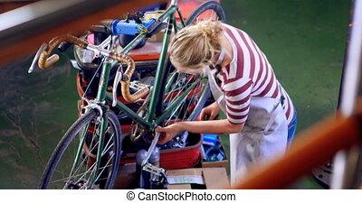 Woman repairing cycle at workshop 4k - Beautiful woman...