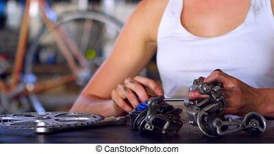 Woman repairing parts of bicycle at workshop 4k - Beautiful...