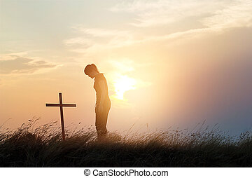 Woman respecting at the cross on the field of sunset background
