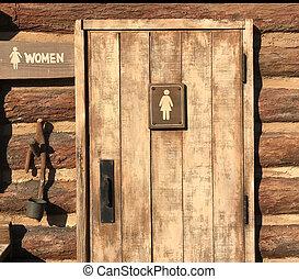 Woman rest room sign on old wooden door