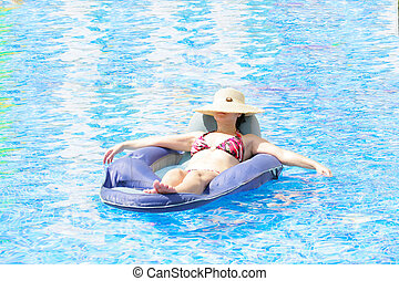 woman resting and tanning in the pool