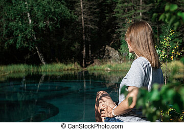Woman resting at mountain lake in summer