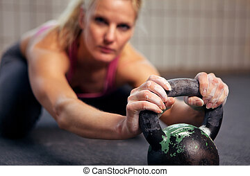 Woman Resting During Kettlebell Workout - Portrait of young...