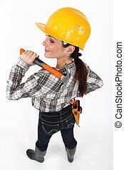 Woman resting hammer over shoulder