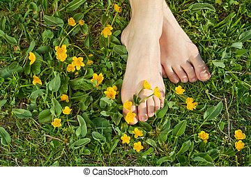 Woman resting her feet in the fresh spring vegetation under sunshine