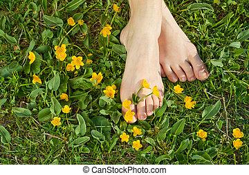 Woman resting her feet in the fresh spring vegetation under...