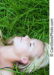 Woman resting in a field of green grass