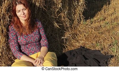 woman resting in the hay on a hot day