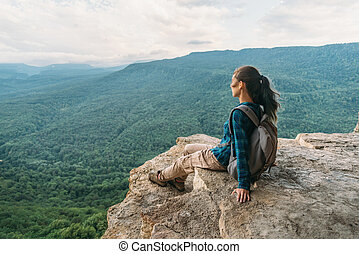 Woman resting on edge of cliff