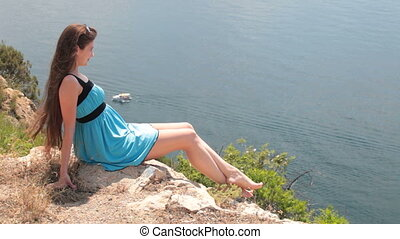 Woman resting on  rock by the sea