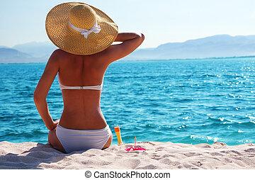 woman in white bikini resting on the beach in straw hat