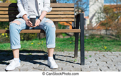 Woman resting on the bench with cup of coffee.