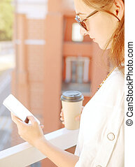 Woman resting with cup of coffee and smartphone on balcony.