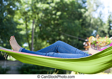 Woman resting with drink on hammock