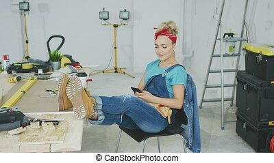 Woman resting with smartphone at carpenter workbench -...