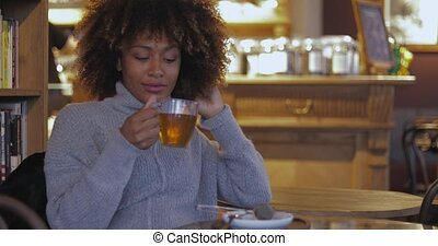 Woman resting with tea in cafe - Pretty young dreamy woman...