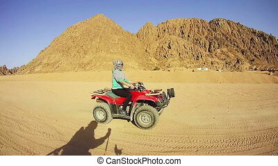 Woman Rides a Quad Bike in the Desert of Egypt