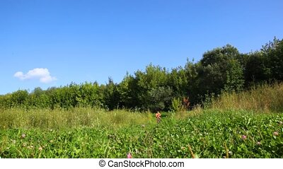 happy young woman rides bicycle to camera in summer field against forest