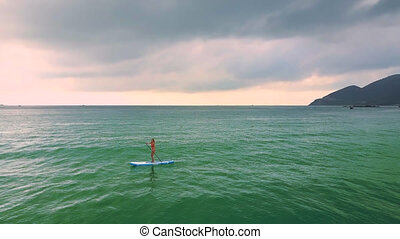 woman rides surfs on paddleboard among ocean
