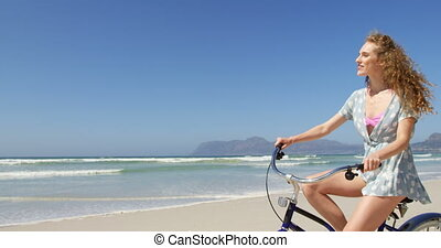 Woman riding a bicycle at beach on a sunny day 4k