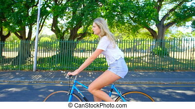 Woman riding a bicycle in the street 4k - Young woman riding...