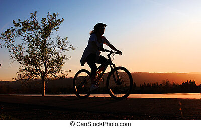 Woman riding a bike - Woman riding her bike along the river...