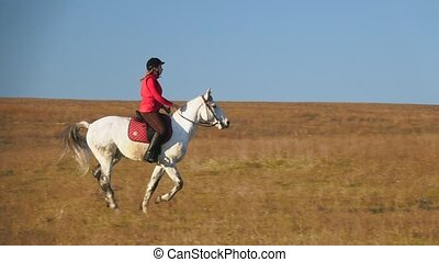 Woman riding a horse galloping across the field. Slow motion...